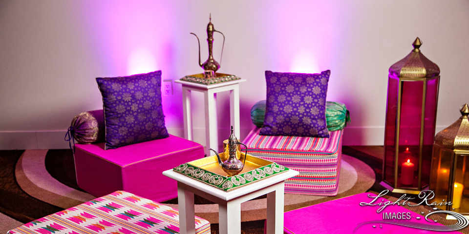 Mehendi or Garba night theme sofa settee set-up with purple, gold and pink pillows and tinted magenta and gold glass lamps