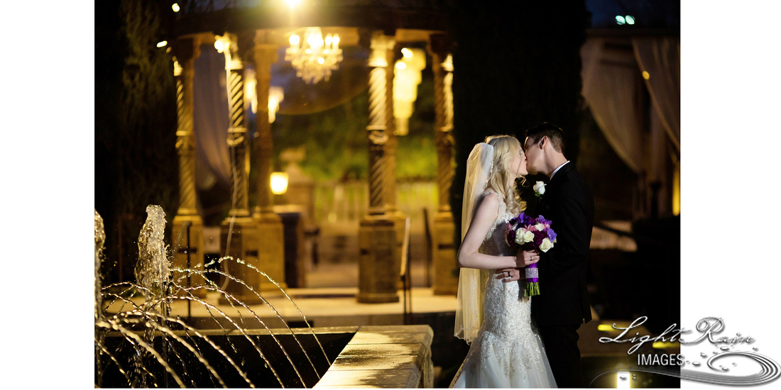 bride and groom kissing by fountain at night